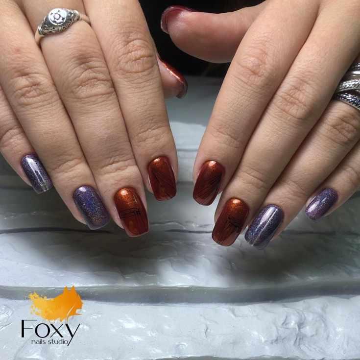 Оранжевый с фиолетовым осенний маникюр кошачий глаз на длинные квадратные ногти с черными паутинками гель-лака и серебристыми вертикальными полосками