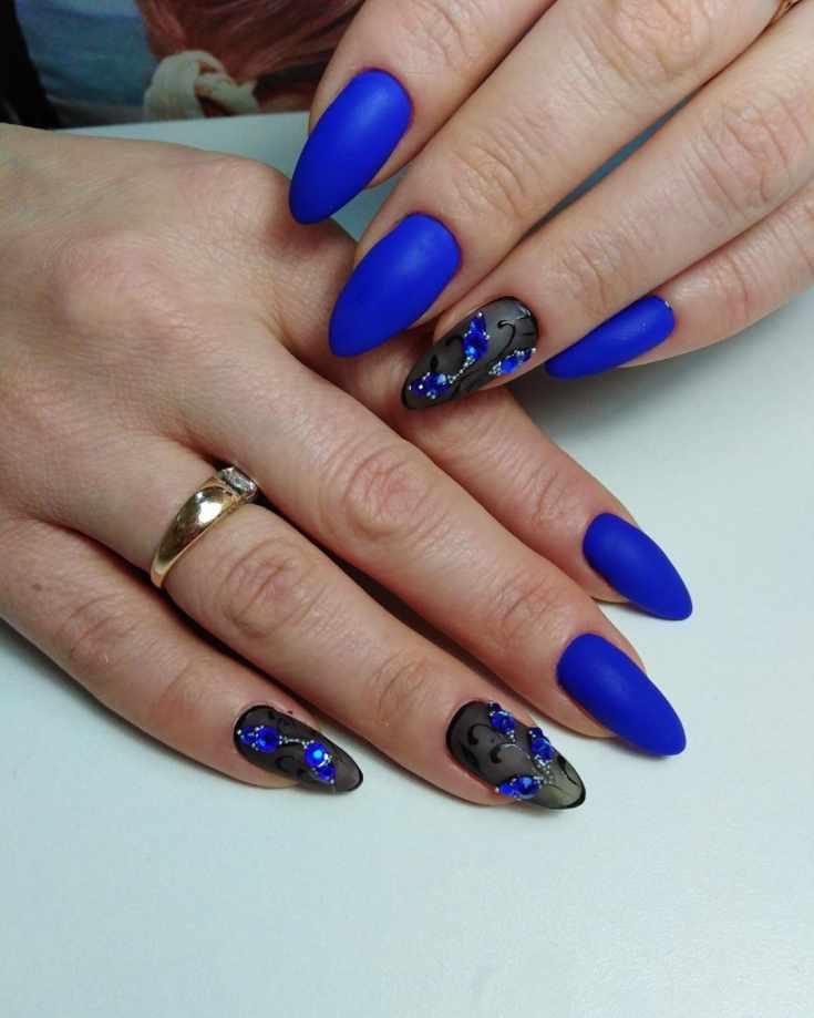 Синий матовый маникюр на длинные ногти миндаль с полупрозрачным черным цветочным дизайном и синими стразами