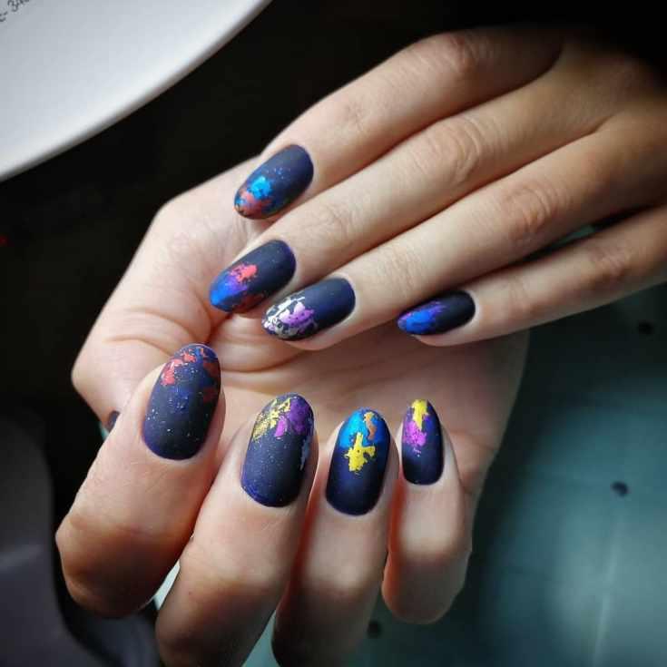 Синий матовый осенний маникюр на короткий овал с разноцветными пятнами фольги