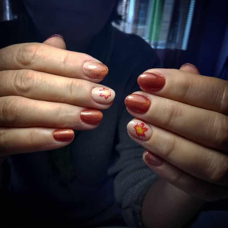 Короткий осенний маникюр медного цвета на овальные ногти с растяжкой блестками на указательных пальцах и кленовыми листьями на безымянных ногтях нюдового цвета