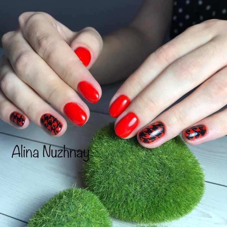 Красный короткий овальный маникюр с черными штампами на двух ногтях