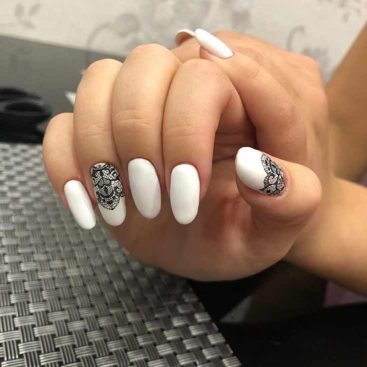 Белый матовый маникюр на длинные овальные ногти с черным кружевом на двух ногтях