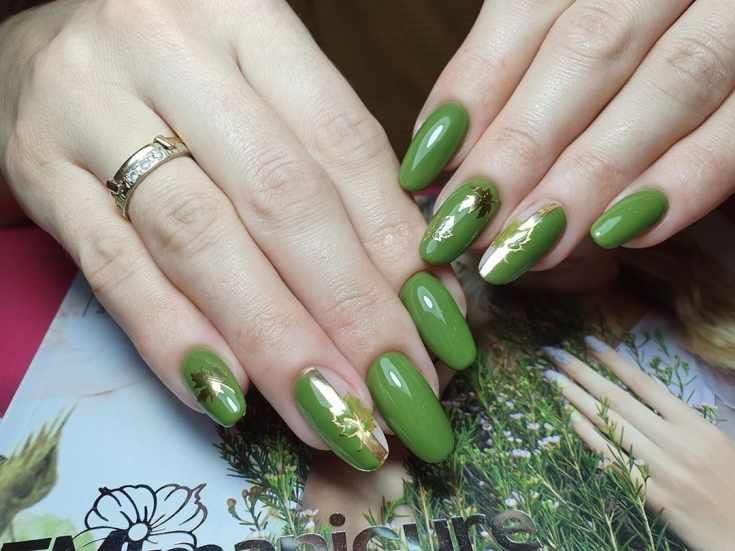Зелёный миндальный маникюр осень с золотыми вертикальными полосками и листочками на двух ногтях