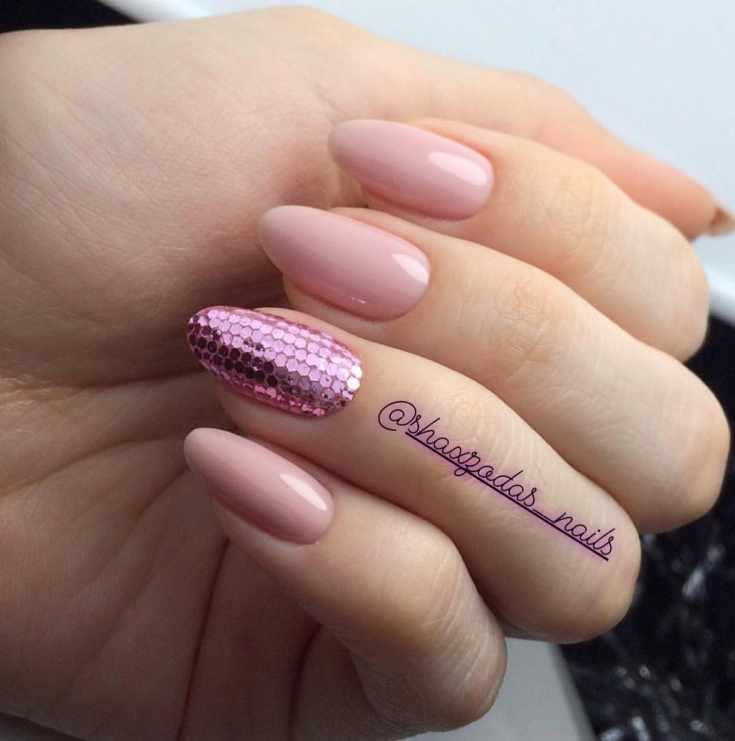Нюдовый маникюр на миндальные ногти средней длины с розовыми пайетками на безымянном пальце