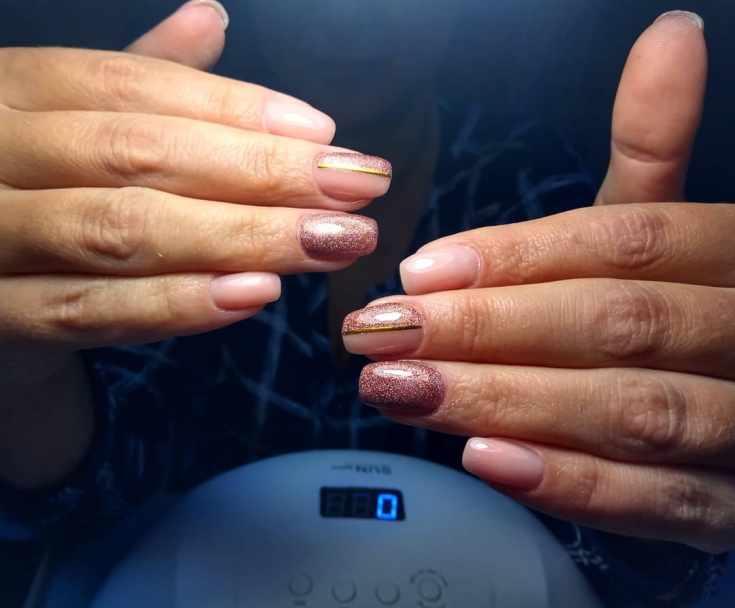 Нюдовый маникюр с глиттером и вертикальными золотистыми полосками на квадратные ногти средней длины