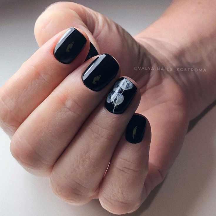 Короткий чёрный маникюр квадрат с белыми узорами на безымянном пальце