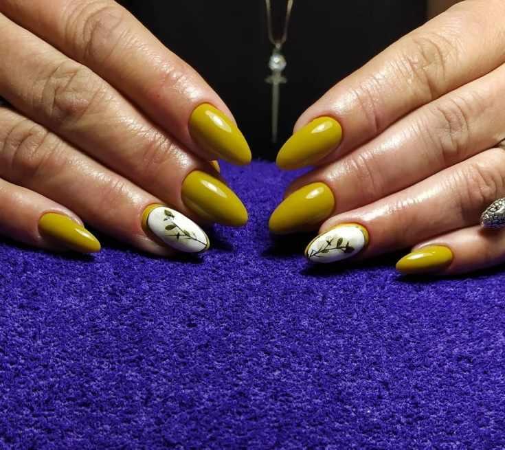 Однотонный темно-желтый миндальный маникюр с рамочным цветочным дизайном на безымянном пальце