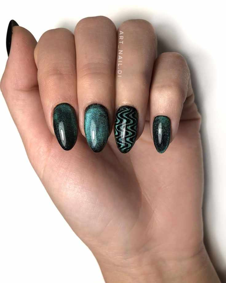 Черный с зеленым маникюр кошачий глаз на миндальные ногти с волнами на безымянном пальце