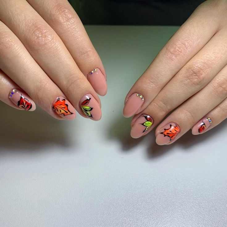 Нюдовый осенний маникюр со стразами и яркими рисунками осенних листочков