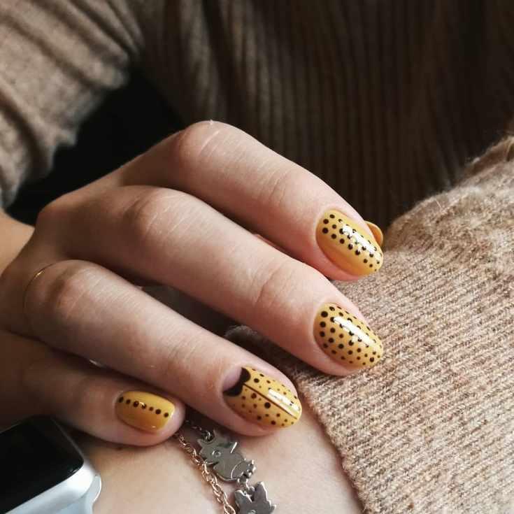 Желтый маникюр в черный горошек на короткие овальные ногти в осеннем офисном стиле