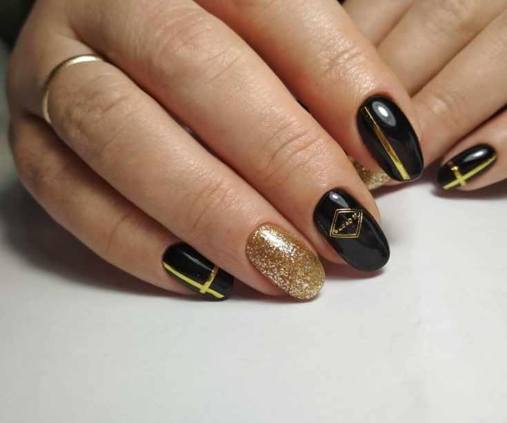 Черный с золотым маникюр на миндальные ногти средней длины с глиттером, лентами и наклейками