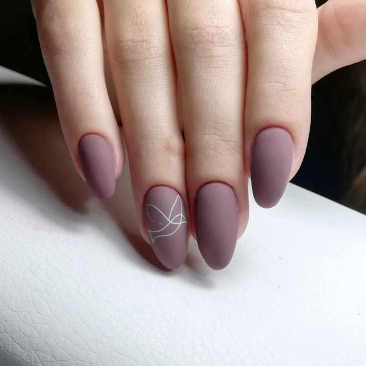 Однотонный бордовый матовый маникюр на длинные миндальные ногти с силуэтом птицы на безымянном пальце
